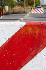 Red and white striped concrete road barrier.