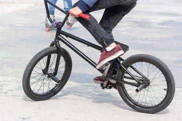 Young boy riding his BMX bike near ramps