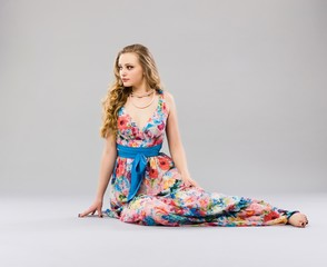 Beautiful young woman sitting in a trendy long dress