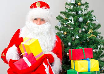 Santa Claus with gifts near the Christmas tree.