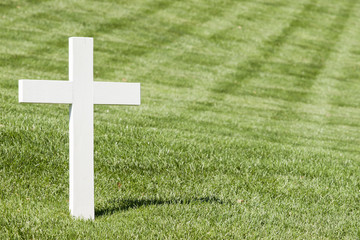 White cross on green lawn.Arlington National Cemetery,