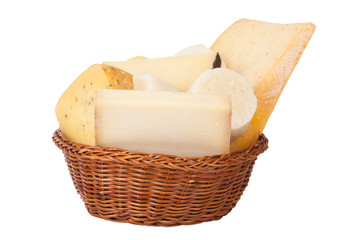Different cheeses and a bunch of parsley lying in a wicker baske