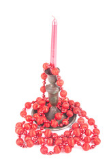 red beads and candle on a white background