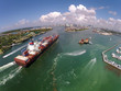 canvas print picture - Cargo ship enters port aerial view