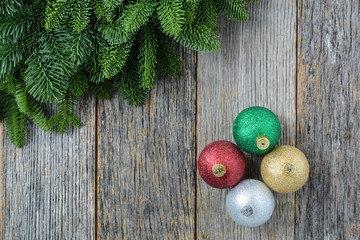 Christmas Pine Needle and Ornaments on a Rustic Wood Background