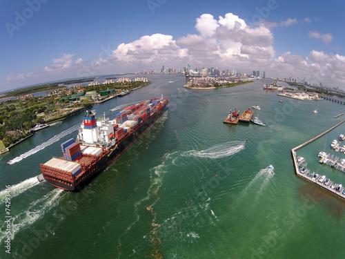 Leinwandbild Motiv Cargo ship enters port aerial view