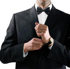 man in tuxedo puts on watch