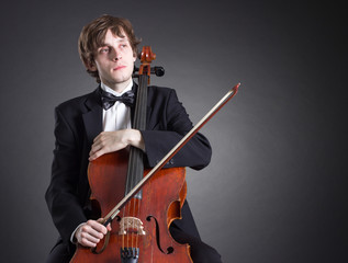 Cellist sits in thought with a musical instrument.