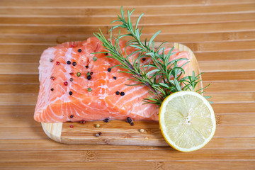 Raw salmon with lemon on wooden table
