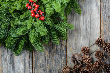 Tree branch with Holly Berry and pine cones on rustic wooden bac