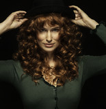 Pretty red-haired girl with curls with frackles, black hat
