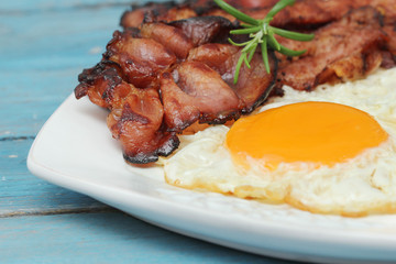 Breakfast - eggs and bacon on blue wooden table