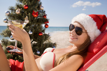 Santa girl in Christmas vacation on the beach