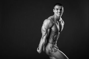 Handsome muscular guy, bodybuilder, posing on a black