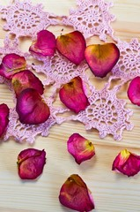 beautiful dried rose petals on the table with light wood