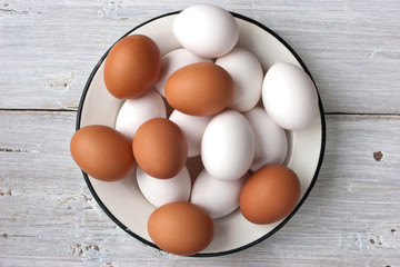 Chicken eggs in the white plate on the white table