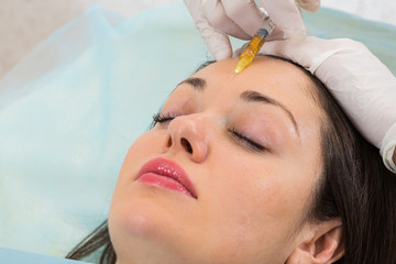 making injection to beautiful woman in spa clinic