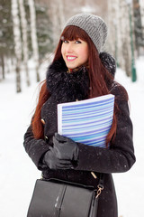 Winter girl with a folder for papers