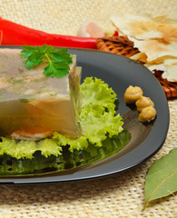 Delicious fish aspic on white plate with mustard and green salad
