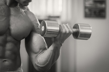 Strong and muscular guy with dumbbell
