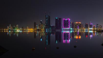Night modern city skyline panorama with neon lights
