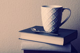Old books and cup of coffee on table