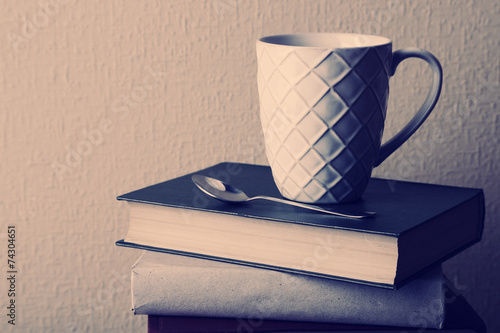 Old books and cup of coffee on table - 74304651