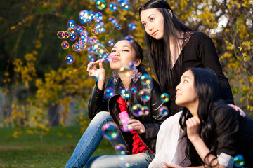 Young Asian Womens Blowing Bubbles in the park