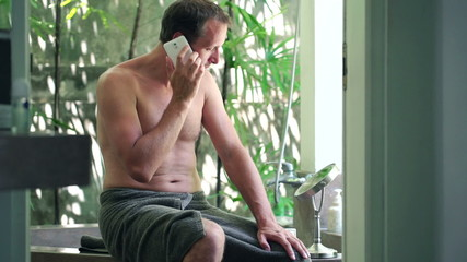 Young handsome man talking on cellphone in the bathroom