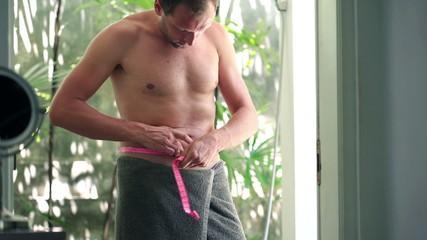 Happy slim man measuring his waist in the bathroom