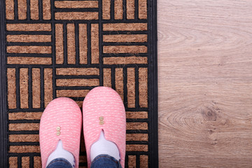 Girl in home slippers on brown carpet on floor close-up