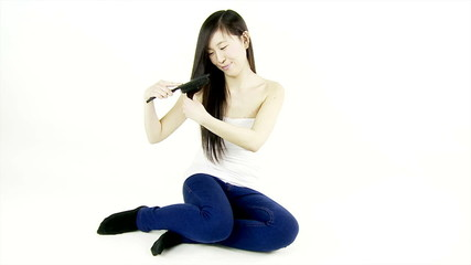 Chinese beautiful girl brushing long hair isolated