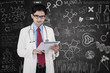 Doctor with tablet in front of blackboard