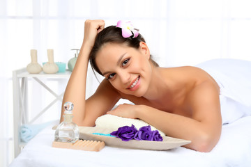 Beautiful young woman in spa salon on light background