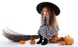 Little girl Witch in hat with pumpkins and broom isolated