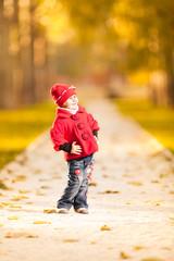 Cute girl walk in the rays of the autumn sun