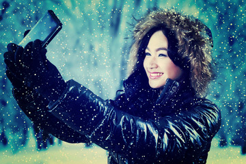 Girl in winter jacket taking self portrait