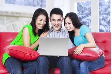 Group of asian people using laptop on sofa