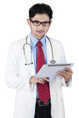 Hispanic male doctor with tablet computer