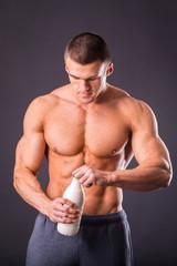 Male bodybuilder holding a bottle of milk in hand