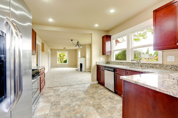 Bright kitchen room with granite tops and burgundy cabinets