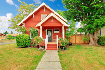 Small coutnryside house exterior in bright red color with white