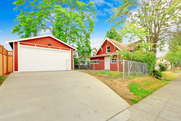 Bright red house exterior with garage and driveway
