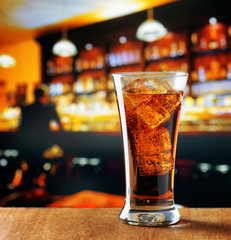 Glass of cola with ice in a bar