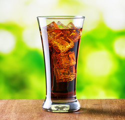Glass of cola with ice on nature background