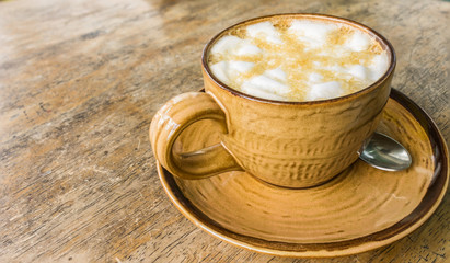 Orange coffee cup on wooden table background