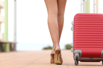 Back view of a traveler woman legs walking with a suitcase