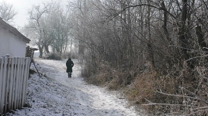 Man walking away on a frozen road