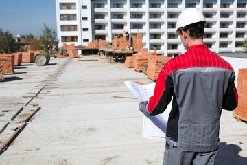 Builder worker with blueprint at construction site