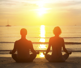 Young yoga couple meditating during amazing sunset on the beach.